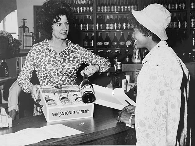 Historical photo of Maddalena Riboli selling wine to customer in tasting room
